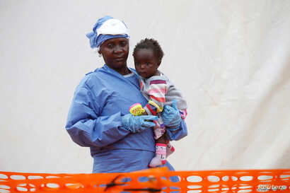 FILE - Victorine Siherya, an Ebola survivor working as a caregiver to babies who are confirmed Ebola cases, holds an infant outside the red zone at the Ebola treatment center in Butembo, Democratic Republic of Congo, March 25, 2019.