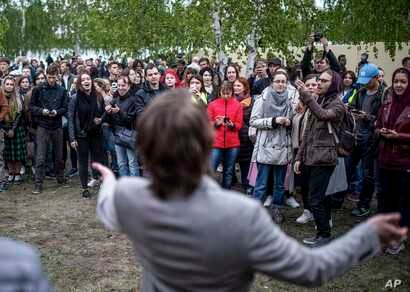 An activist speaks to a crowd at a fence blocking demonstrators protesting plans to construct a cathedral in a park in Yekaterinburg, Russia, May 16, 2019.