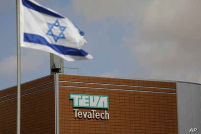 FILE - An Israeli flag flies outside a Teva Pharmaceutical Industries building, in Neot Hovav, Israel, Dec. 14, 2017.