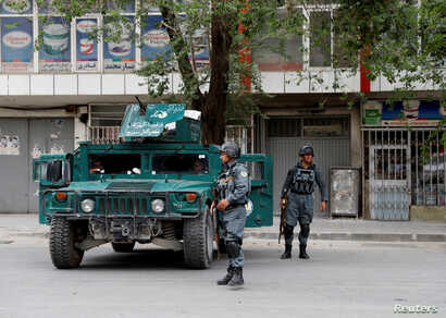 Afghan policemen keep watch a during gunmen attack in Kabul, Afghanistan, May 8, 2019.