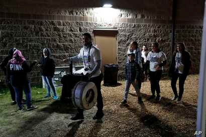 Hassan Chami, banging a bass drum, leads attendees to the Ramadan Suhoor Festival in Dearborn Heights, Mich.