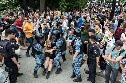 Police officers detain a protester during a march in Moscow, Russia, June 12, 2019.