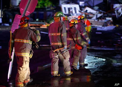 Firefighters walk to an area of debris from a hotel and a mobile home park in El Reno, Okla., Sunday, May 26, 2019, following a likely tornado touchdown late Saturday night.