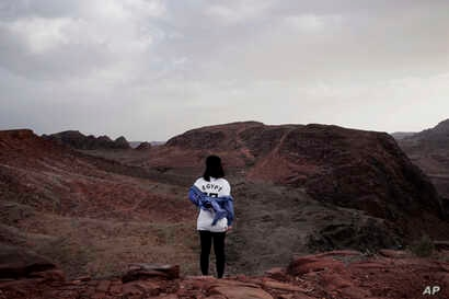 A Korean tourist poses for a photograph for her friend on a trek in the mountains near Wadi Sahw, Abu Zenima, in South Sinai, Egypt, March 29, 2019.