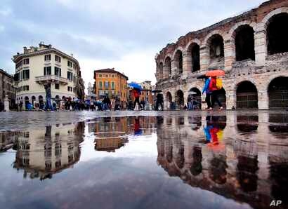 Tourists walk in the pouring rain along the old arena, right, and buildings of the old town in Verona, Italy, Tuesday, April 23, 2019.