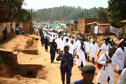 FILE - Doctors and health workers march in the Eastern Congo town of Butembo on April 24, 2019, after attackers shot and killed an epidemiologist from Cameroon who was working for the World Health Organization. Doctors at the epicenter of Congo's Ebo...
