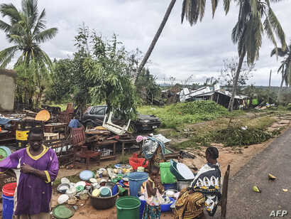 Assane Maulana rescues his belongings with his family in front of his home and shop in Macomia, following Cyclone Kenneth, April 28, 2019. Thousands of people in remote areas of storm-lashed Mozambique were homeless and bracing for imminent flooding....