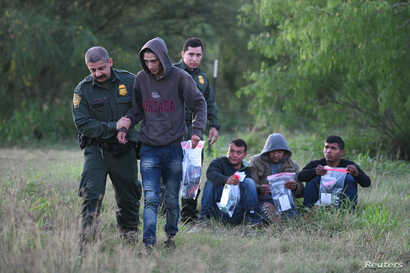 U.S. Border Patrol agents apprehend undocumented migrants after they illegally crossed the U.S.-Mexico border in Mission, Texas, April 9, 2019.
