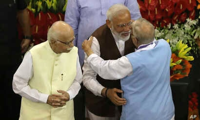 Indian Prime Minister Narendra Modi, second right, hugs senior Bharatiya Janata Party leader M.M. Joshi as L.K. Advani, left, watches after Modi's election as ruling alliance leader, in New Delhi,  May 25, 2019.