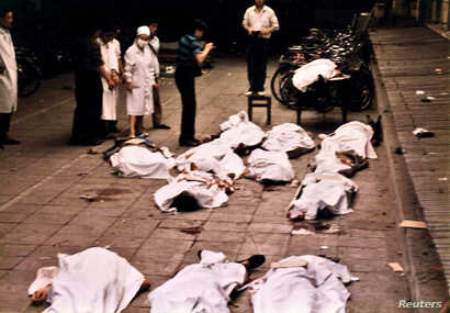 Medical workers of Beijing's Fuxingmen Hospital look at bodies of protesters killed by soldiers near Tiananmen Square on June 4, 1989.
