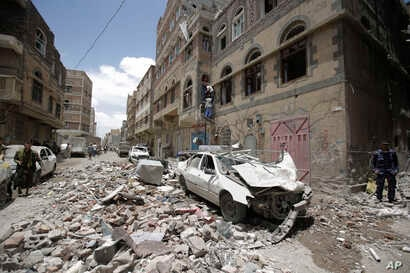 People inspect the site of an airstrike by Saudi-led coalition in Sanaa, Yemen, May, 16, 2019.