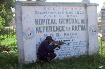 FILE - Police shelter behind a hospital sign as they guard a hospital in Butembo, Congo, April 20, 2019, after militia members attacked an Ebola treatment center in the city's Katwa district overnight.