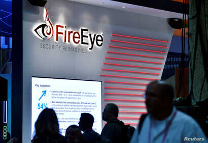 Attendees walk by the FireEye booth during the 2016 Black Hat cyber-security conference in Las Vegas, Nevada,  Aug. 3, 2016.