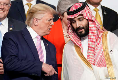 U.S. President Donald Trump speaks with Saudi Arabia's Crown Prince Mohammed bin Salman during family photo session with other leaders and attendees at the G-20 leaders summit in Osaka, Japan, June 28, 2019.