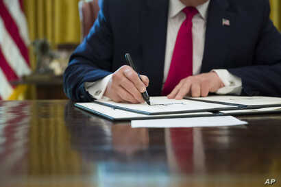 President Donald Trump signs an executive order to increase sanctions on Iran, at the White House, June 24, 2019.