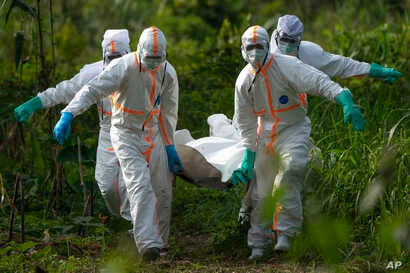 Burial workers dressed in protective gear carry the remains of an Ebola victim in Beni, Congo, July 14, 2019.