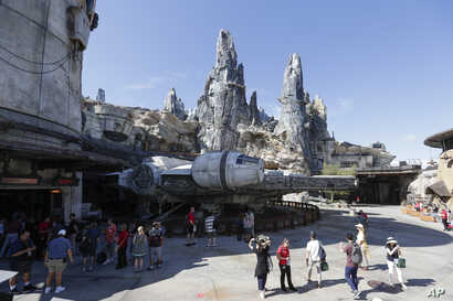 Park visitors walk near the entrance to the Millennium Falcon Smugglers Run ride during a preview of the Star Wars themed land, Galaxy's Edge in Hollywood Studios at Disney World, Aug. 27, 2019, in Lake Buena Vista, Florida.