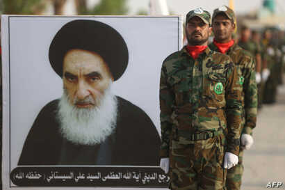 FILE - Members of the Liwa al-Tafuf 13th Brigade of Iraq's Shi'ite Muslim Hashed al-Shaabi paramilitary carry a placard showing Iraqi Ayatollah Ali Sistani during a graduation ceremony at a training center in Karbala, Iraq, Aug. 30, 2019.
