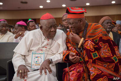 Cardinal Christian Wiyghan Tumi, left, talks with Cameroonian veteran opposition leader John Fru Ndi at the Congress Palace during the opening session of the National Dialogue, in Yaounde, Cameroon, Sept. 30, 2019.