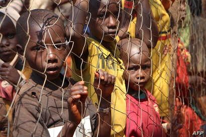 FILE - Burundian children, who fled their country, stand behind a fence at Nyarugusu camp, Tanzania, June 11, 2015.