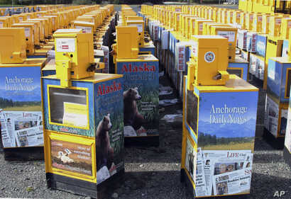 FILE - Hundreds of old newspaper vending machines are shown in a vacant lot near the former offices of the Alaska Dispatch News in Anchorage, Alaska, Sept. 11, 2017.