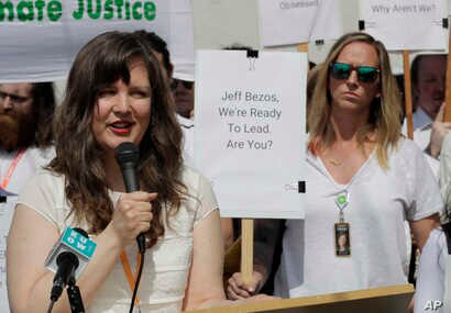 "Emily Cunningham, left, who works as a user experience designer at Amazon.com, speaks as Kathryn Dellinger, right, who also works for Amazon, looks on, following Amazon's annual shareholders meeting, May 22, 2019, in Seattle. Both women are part of the group ""Amazon Employees for Climate Justice."""