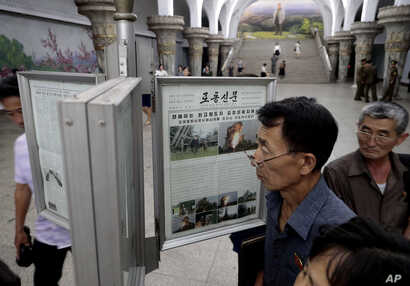 Men read public newspapers with headlines featuring the news on the country's rocket launcher test at a subway station in Pyongyang, North Korea, Sept. 11, 2019.
