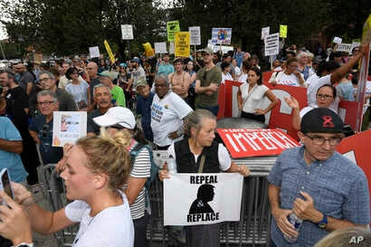 Demonstrators gather near the U.S. House Republican Member Retreat where President Donald Trump is speaking, in Baltimore, Sept. 12, 2019.