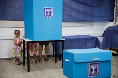 A woman votes at a polling station in Rosh Haayin, Israel, Tuesday, Sept. 17, 2019.