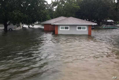 In this photo provided by the Chambers County Sheriff's Office, floodwaters surround a home, Sept 19, 2019, in Winnie, Texas. The area experienced heavy flooding due to Tropical Depression Imelda.