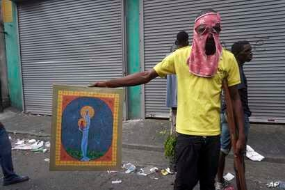 A man poses with a painting after looting a shop during a protest to demand the resignation of president Jovenel Moise in Port-au-Prince, Haiti, Sept. 27, 2019.