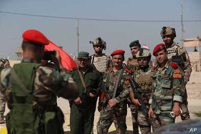 Iraqi and Syrian security forces take a picture during the opening ceremony of the crossing between the Iraqi town of Qaim and Syria's Albukamel ,Sept. 30, 2019.