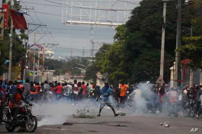 Protesters turn and run as police began to fire tear gas as they gather in Port-au-Prince, Haiti, Monday, Sept. 30, 2019.