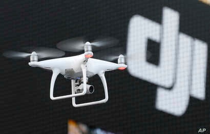 FILE - A Phantom 4, developed by major Chinese consumer-drone maker DJI, flies during its demonstration flight in Tokyo, March 3, 2016.