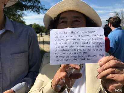 The Zhangs did not speak English but carried a handwritten note about their ancestors' donation. They needed tickets, and a tourist from Dallas gave them her extras. (P. Widakuswara/VOA)