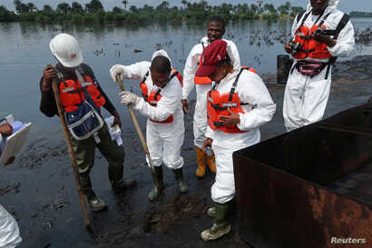 Members of the joint task force, part of the Bodo oil spill clean-up operation, inspect the site of an illegal refinery near the village of Bodo in the Niger Delta, Aug.2, 2018.