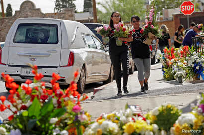 FILE - People carry flowers during a tribute to the victims of a mass shooting at a Walmart store in El Paso, Texas, Aug. 18, 2019.