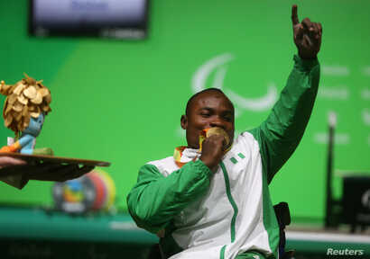 FILE - Roland Ezuruike of Nigeria kisses his gold medal following the men's Paralympic Powerlifting competition, Rio de Janeiro, Brazil, Sept. 9, 2016.