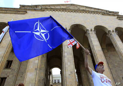 A NATO supporter waves a NATO flag during a rally in front of Georgia's Parliament building in Tbilisi, Georgia, July 6, 2019.