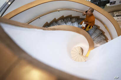 FILE - A Thai Buddhist monk talks on a mobile phone during a visit to Bangkok Art and Culture Center, Thailand, Sept. 17, 2019.
