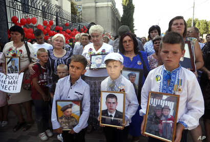 FILE - Relatives hold portraits of Ukrainian soldiers killed by Russian artillery near the village of Ilovaysk in eastern Ukraine, during a protests in front of the Russian Embassy in Kyiv, Ukraine, Aug.28, 2019.