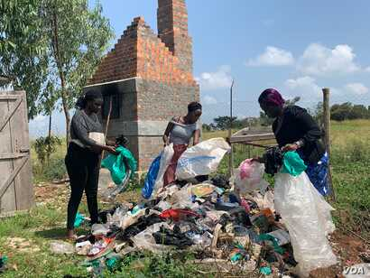 Aweko Faith, center, and her colleagues sort through garbage to pick polythene bags to be used to make plastic backpacks, in Mpigi district, Uganda. (H. Athumani/VOA)