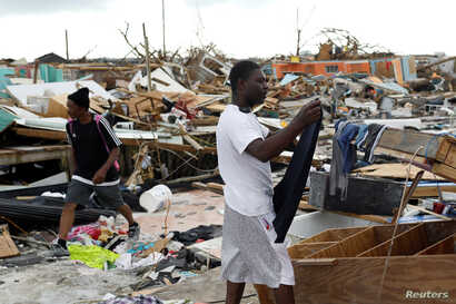 A man hangs his clothes after washing them at the Mudd neighborhood, devastated after Hurricane Dorian hit the Abaco Islands in Marsh Harbor, Bahamas, Sept. 6, 2019.