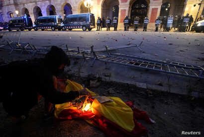 FILE - A demonstrator burns a Spanish flag at a protest in front of Catalonia's parliament on Catalonia's National Day, in Barcelona, Spain, Sept. 11, 2019.