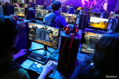 FILE - People play online games at the Thailand Game Show 2018 in Bangkok, Thailand, Oct. 26, 2018.