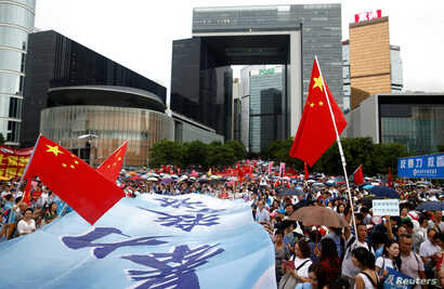"""People wave Chinese flags during a pro-China """"Safeguard Hong Kong"""" rally at Tamar Park to voice support for the police and call for an end to violence, in Hong Kong, Aug. 17, 2019."""