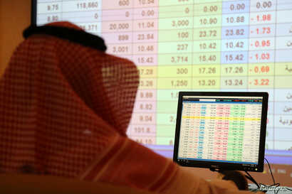 A saudi man looks to the computer showing stock prices at ANB Bank, in Riyadh Saudi Arabia, Sept. 15, 2019.