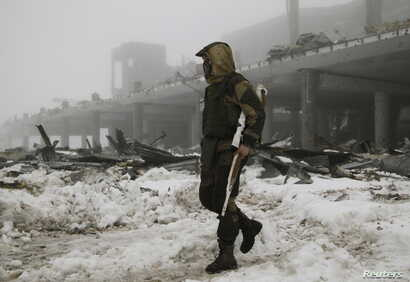 FILE - A member of the self-proclaimed Donetsk People's Republic forces walks near a building, destroyed during battles with the Ukrainian armed forces, at Donetsk airport , Jan. 12, 2016.
