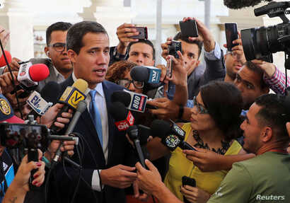 Venezuelan opposition leader Juan Guaido, who many nations have recognized as the country's rightful interim ruler, talks to the media as he arrives to attend a session of Venezuela's National Assembly in Caracas, Venezuela, Sept. 17, 2019.