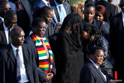 Zimbabwean President Emmerson Mnangagwa stands next to Grace Mugabe, after receiving the body of her husband, former Zimbabwean President Robert Mugabe in Harare, Zimbabwe, Sept. 11, 2019.